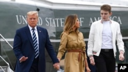 FILE - President Donald Trump, first lady Melania Trump and their son, Barron Trump, walk off of Marine One at Morristown Municipal Airport in Morristown, N.J., Aug. 16, 2020.