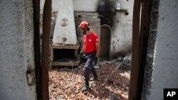 Pripadnik spasilačkog tima pretražuje spaljenu kuću u Mati, istočno od Atine, 25. jula 2018.