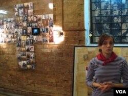 博物馆工作人员玛丽娜。墙上的是受害者的照片。(美国之音白桦拍摄)
