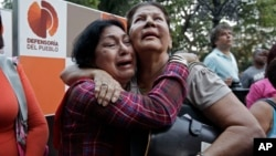 Supporters of Venezuela's President Hugo Chavez weep as she learn that Chavez has died through an announcement by the vice president in Caracas, Venezuela, Tuesday, Mar. 5, 2013.