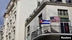 Cuban and U.S. flags are seen on the balcony of a restaurant in Havana, Cuba, March 19, 2016.