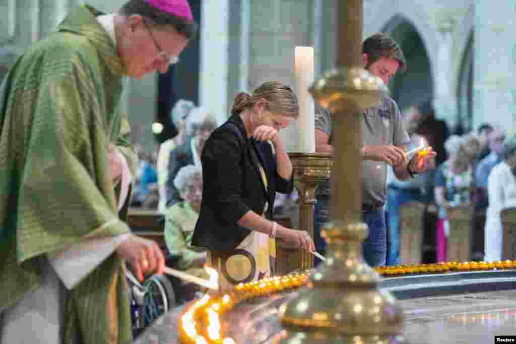Churchgoers together with bishop Jan Hendriks (L) light some 298 candles, representing the victims of the crashed Malaysia Airlines Flight MH17 plane, before a mass in the Saint Bavo cathedral in Haarlem, the Netherlands, July 20, 2014.