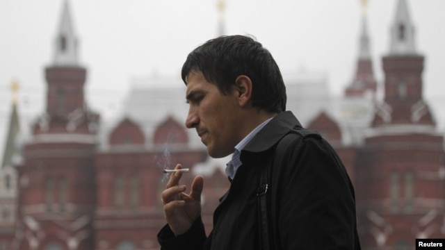 FILE - A man smokes along a street in central Moscow