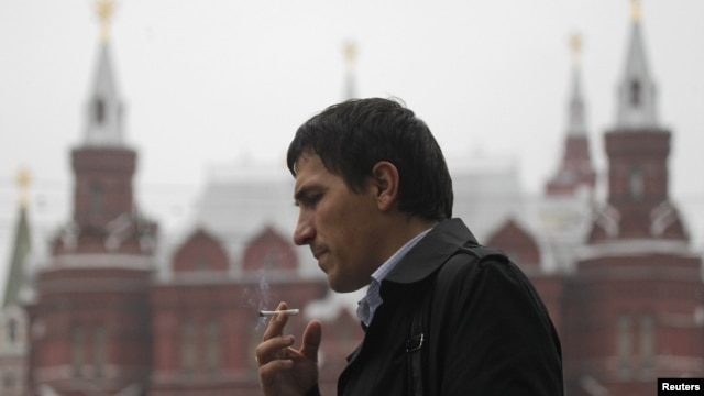 A man smokes along a street in central Moscow, October 16, 2012.
