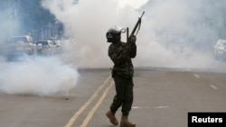 A riot policeman holds up his weapon as tear gas is fired to disperse supporters of Kenyan opposition National Super Alliance coalition, during a protest along a street in Nairobi, Kenya October 13, 2017.