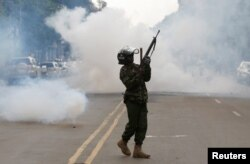 A riot policeman holds up his weapon as tear gas is fired to disperse supporters of Kenyan opposition National Super Alliance coalition, during a protest along a street in Nairobi, Kenya, Oct. 13, 2017.