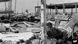 اين عکس کارل رايت ۱۱ ساله را نشان می دهد که در ميان خرابه های ايستگاه خدمات پدرش در شهر گولف پورت، پس از توفان کا ميل، از لوله ترکيده، آب مينوشد. ۱۹ اوت ۱۹۶۹
