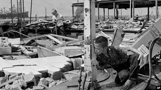 This Aug. 19, 1969 photograph showing Carl Wright, 11, drinking from a broken pipe amid the ruins of his father's service station in Gulfport, Miss., in the aftermath of Hurricane Camille.