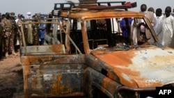 Des responsables nigériens se tiennent près de la voiture du groupe humanitaire français ACTED dans la réserve de Kouré, à environ 60 km de Niamey, le 21 août 2020.