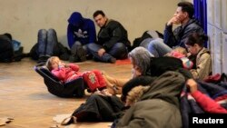 FILE - Kosovars seeking asylum wait in a railway station in Budapest, Feb. 10, 2015.