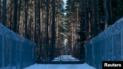 FILE - Barbed wire fence surrounding a military area is pictured in the forest near Stare Kiejkuty village, close to Szczytno in northeastern Poland, Jan. 24, 2014.