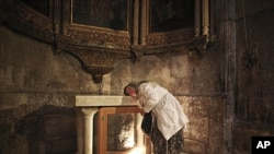 一位基督徒朝圣者在圣墓教堂把头放在圣坛上祷告