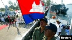 Personnel from the Vietnamese and Cambodian navies stand at attention as a national anthem is played onboard a cruiser during a handing-over ceremony at a Cambodian naval base in Sihanouk Ville, 210km (130 miles) southwest of Phnom Penh January 11, 2006. The Vietnamese government on Wednesday donated two cruisers to the Cambodian navy for sea patrols.