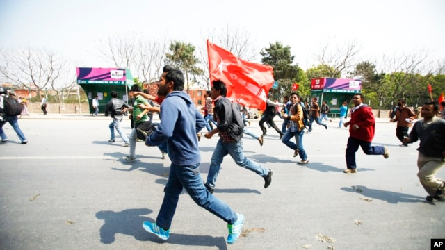 Members of a splinter faction of the Unified Communist Party of Nepal Maoist run and shout slogans as they protest against the formation of an interim government in Katmandu, Nepal, March 14, 2013.