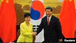 Presiden Korea Selatan Park Geun-Hye (kiri) berjabat tangan dengan Presiden China Xi Jinping (kanan) seusai upacara deklarasi kerjasama bilateral di Beijing (27/6).