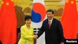 韩国总统朴槿惠(左)与中国国家主席习近平6月27日在北京人民大会堂握手。