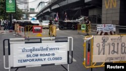 FILE - A sign indicating the closure of a main touristic road can be seen next to barricades of anti-government protesters near a main stage of the protest in Bangkok, Feb. 5, 2014.