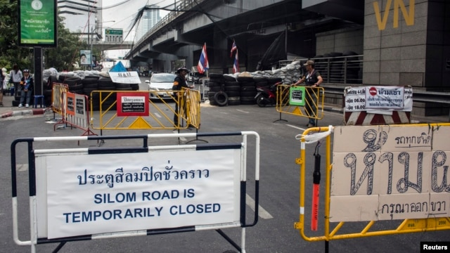 A sign indicating the closure of a main touristic road can be seen next to barricades of anti-government protesters near a main stage of the protest in Bangkok, Feb. 5, 2014.
