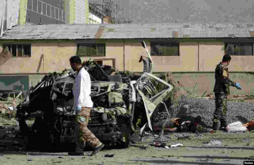 Afghan security personnel stand near a mangled vehicle as they investigate a suicide bomb attack, Kabul, Afghanistan, September 18, 2012.
