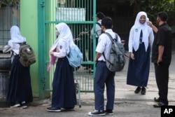 Seorang satpam memeriksa suhu tubuh seorang siswa sebelum memasuki sekolahnya pada hari pertama pembukaan kembali sekolah menengah negeri di Bekasi, 13 Juli 2020. (Foto: AP/Achmad Ibrahim)