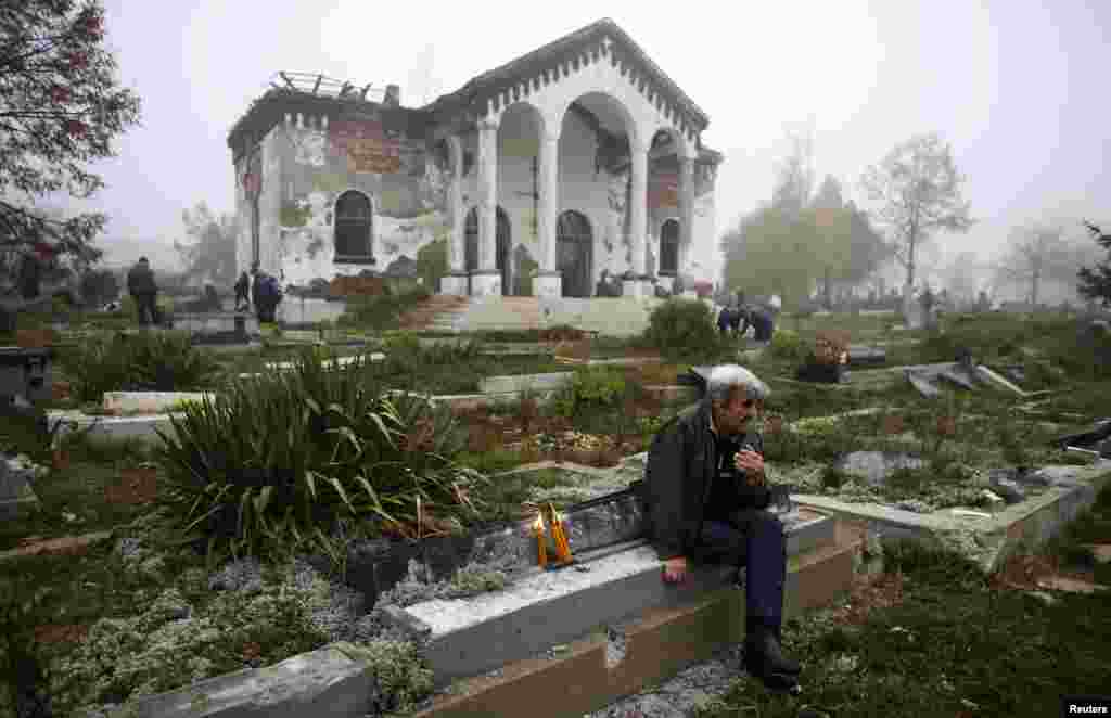 "A Kosovo Serb man sits next to a vandalized grave in the ethnically divided Kosovo town of Mitrovica. Serbs from the north of Mitrovica crossed the river into the mainly Albanian south to pay respects to lost loved ones on the winter ""Zadusnice"" -- the Serbian Orthodox equivalent of All Souls' Day -- at the Orthodox cemetery."