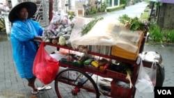 Seorang ibu tengah mendorong gerobak jualannya di sebuah area perumahan di Jakarta (VOA/Iris Gera). Pemerintah menjamin cukup tersedianya bahan kebutuhan pangan bagi seluruh wilayah tanah air di musim penghujan seperti sekarang ini.