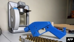 FILE - A Liberator pistol is seen next to the 3-D printer on which its components were made, July 11, 2013.