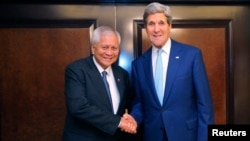 FILE - Foreign Minister of the Philippines Albert del Rosario (L) and U.S. Secretary of State John Kerry shake hands before a meeting.