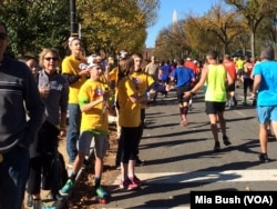 FILE - Teens wearing cow-horn hats and ringing cow bells cheer on runners in the Marine Corps Marathon along Independence Avenue in Washington in October 2014.