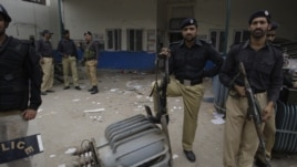 Pakistani police officers stand guard at the office of local electrical company attacked by angry protesters to condemn  electricity shortages in Lahore, March 2012.