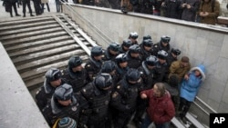 Police officers on a stairway block the path of people intending to attend an opposition rally in Pushkin Square in Moscow, Russia, Dec. 12, 2015.