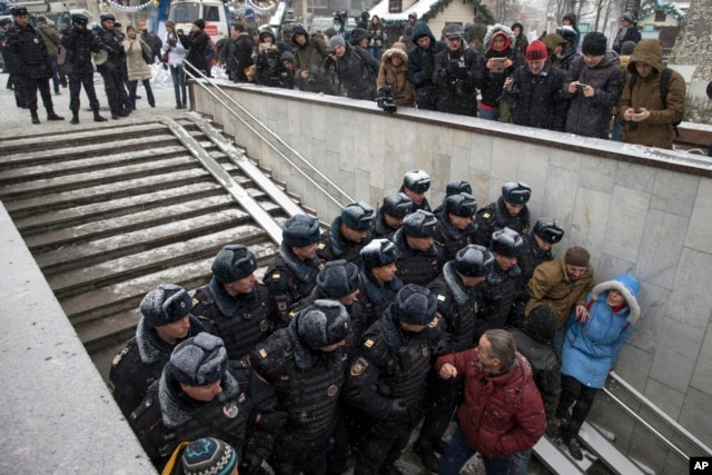 Police officers block the path of people intending to attend an opposition rally in Pushkin Square in Moscow, Russia, Dec. 12, 2015.