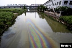 FILE - A China Railway High-speed (CRH) Harmony bullet train travels above a river contaminated by leaked fuel, in Shaoxing, Zhejiang province, China on April 29, 2015.