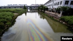 FILE - A China Railway bullet train travels above a river polluted by leaked fuel in Shaoxing, Zhejiang province, April 29, 2015.
