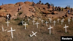 "Members of South Africa's mining community walk near crosses placed at a hill known as the ""Hill of Horror"", where 43 miners died during clashes with police last year at Lonmin's Marikana platinum mine in Rustenburg, northwest of Johannesburg, May 14, 201"
