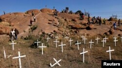 FILE - Members of South Africa's mining community walk near crosses placed at a hill where 43 miners died during clashes with police in 2012 at Lonmin's Marikana platinum mine in Rustenburg, northwest of Johannesburg, May 14, 2013.