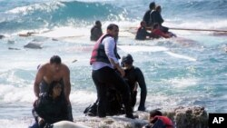Penjaga pantai Yunani menyelamatkan para imigran yang kapalnya terdampar di lepas pantai Pulau Rhodes, Laut Aegean, Senin (20/4).