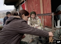 FILE - A fighter from the Syria-based People's Protection Units (YPG) smiles at a female fighter from the Turkey-based Kurdish Workers' Party at their base while they sit around a fire on the outskirts of the town of Sinjar, northern Iraq, on Jan. 29, 2015.