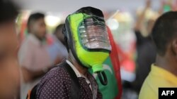 FILE - A protester wears a homemade mask for protection against potential pepper spray or teargas as thousands marched in the capital Male on June 12, 2015. Police in the Maldives unleashed pepper spray on the dozens of demonstrators, which included journalists and activists.