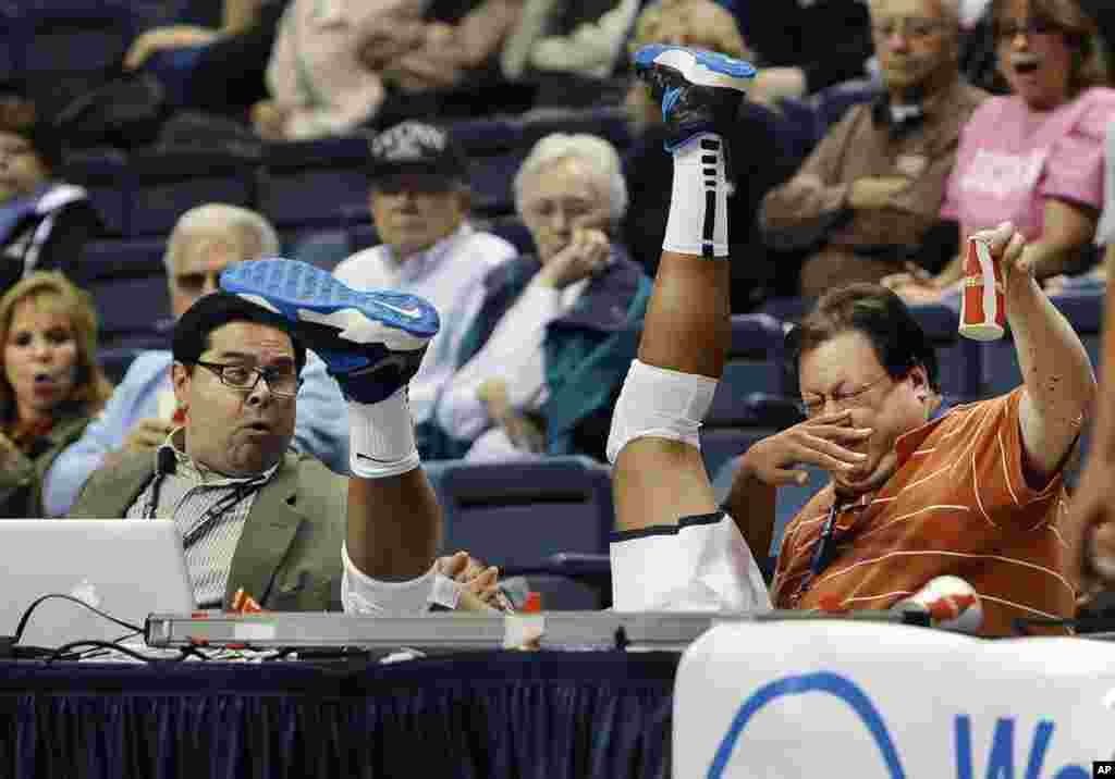 Connecticut's Kaleena Mosqueda-Lewis, center, chases a ball out of bounds, falling between Hartford Courant writer John Altavilla, left, and Associated Press freelancer Ken Davis, right, during the second half of an NCAA college exhibition basketball game in Storrs, Connecticut, USA, Nov. 1, 2013.