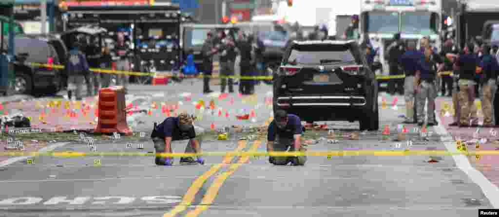 "Federal Bureau of Investigation (FBI) officials mark the ground near the site of an explosion in the Chelsea neighborhood of Manhattan, New York, injuring 29 people late Saturday. Authorities called the blast ""an intentional act."""