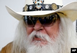 FILE - Reporters are reflected in the sunglasses of Leon Russell as he answers a question at a news conference in Tulsa, Oklahoma, Jan. 29, 2013.
