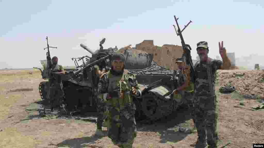 Iraqi Shiite militia fighters celebrate the defeat of Islamic State militants in Amerli, Iraq, Sept. 2, 2014.