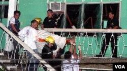 Para petugas mengeluarkan jenasah korban ledakan di hotel Atilano Pension House, kota Zamboanga, Filipina (27/11).