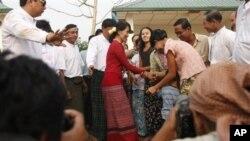 Tokoh demokrasi Burma, Aung San Suu Kyi (baju merah) disambut para pendukungnya saat mengunjungi TPS di pinggiran Rangoon (1/4).