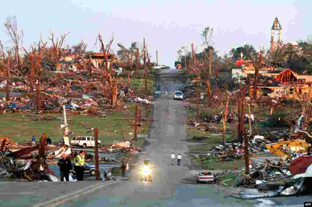23/5: Nhân viên cấp cứu và cư dân đi ngang qua một khu phố ở thành phố Joplin, tiểu bang Missouri sau trận gió lốc tai hại làm ít nhất 125 người chết (Reuters)