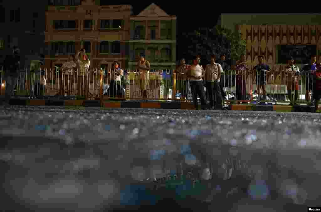 People are reflected in broken glass as they stand in front of Traders Hotel, where an explosion occurred, in central Rangoon, Burma, Oct. 15, 2013.