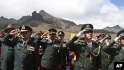 Indian soldiers (L) and Chinese soldiers (R) salute during celebrations to mark the 60th anniversary of the founding of the People's Republic of China, at the Indo-China border, about 41 km (25 miles) from Tawang district in the northeastern Indian state
