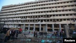 Pejabat polisi dan warga berkumpul di depan gedung Direktorat Keamanan Kairo yang menghadapi ledakan bom mobil (24/1). (Reuters/Amr Abdallah Dalsh)