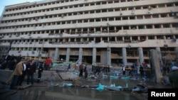 Petugas kepolisian Mesir dan masyarakat setempat berkumpul di depan gedung Markas Besar Kepolisian Pusat Mesir di Kairo yang hancur pasca serangan bom, Jumat (24/1).